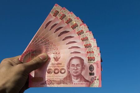 left hand: Asian men left hand hold few hundred banknotes of Thailand on the sky background Thai baht