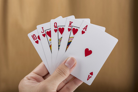 Playing cards in hand isolated on brown background