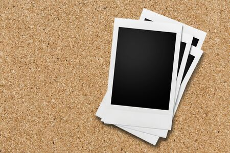 affixed: Cork notice or bulletin board with several style blank instant camera photo prints. Space for copy. Stock Photo