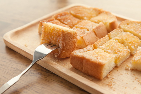Toast bread with butter in wood plate Imagens