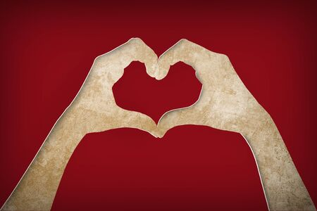 paper hands making a heart shape on a brown paper background Stock Photo