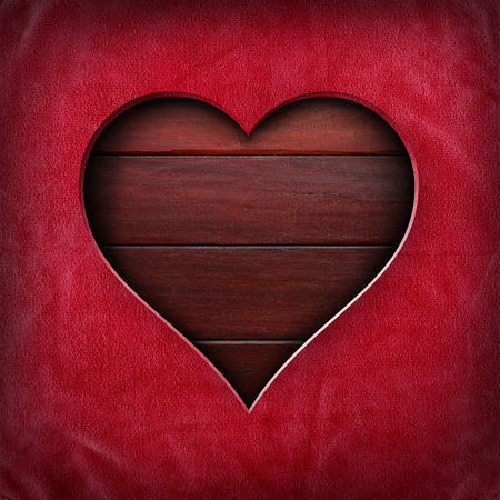 making hole: Heart shape cut out of red fabric on wood surface background