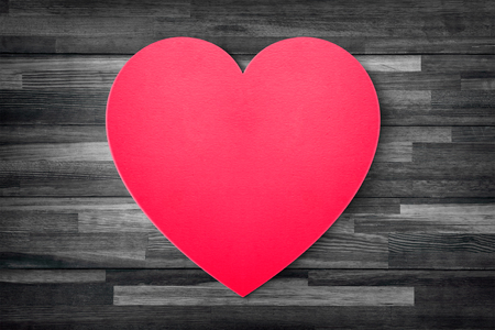Red heart paper on grunge wood table background