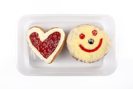 Heart shaped and smile donut in plastic box on white background