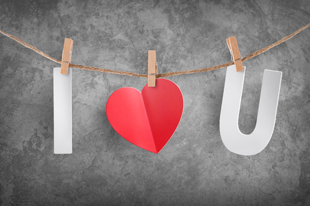 Love hearts and I Love You hanging on rope on cement background for Valentine's day with clipping path