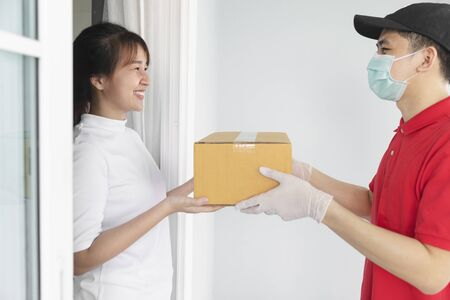 Asian delivery man holding cardboard boxes in medical rubber gloves and mask give to young woman in front of the house, Fast and free Delivery transport, Quarantine