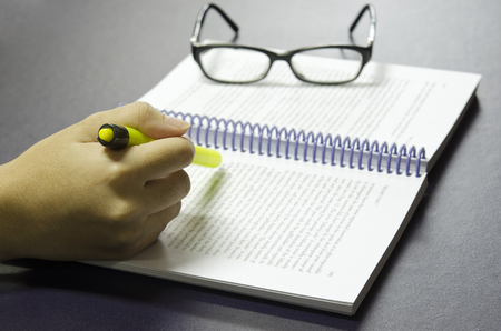 highlighter pen: Hand holding highlighter pen highlights keywords on the book with eye glass in the background