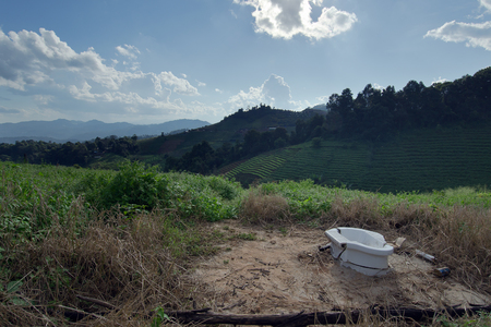 water closet: View of Water closet personal toilet, grassy field, mountain, and cloudy blue sky in Chiangmai Thailand