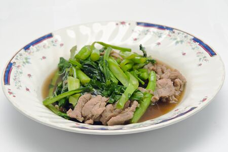 vegtables: Kale fried in Oyster sauce with pork (famous thai food) Stock Photo