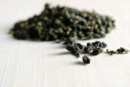 maccha: Piles of dried green tea leaves isolated on wooden board background