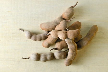 cucurbitaceae: Tamarind or bitter gourd (Other names are Cucurbitaceae, bitter gourd, balsam apple, balsam pear, bitter cucumber, bitter melon, tamarind) isolated on wood background