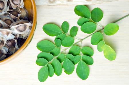 hum: Moringa (Other names are Moringa oleifera Lam., MORINGACEAE, Futaba kom hammer, vegetable hum hum bug, Moringa bug Hoo) leaf and moringa seed on wooden board