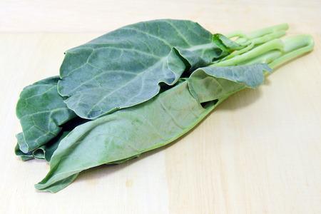 kana: Chinese Kale vegetable (Other names are Chinese Broccoli, Kale, Kai lan, Gai lan, Phak, Khana, Pak , kana, alboglabra, Brassica oleracea) isolated on wood background good for Cantonese cuisine menu Stock Photo