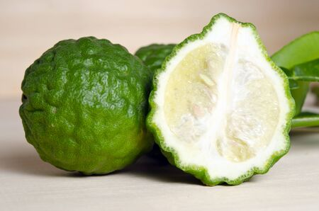 rutaceae: Bergamot (Also known as Kaffir lime, Citrus lime, Magnoliophyta Rutaceae Bergamot) fruits with leaf and half cross section Stock Photo