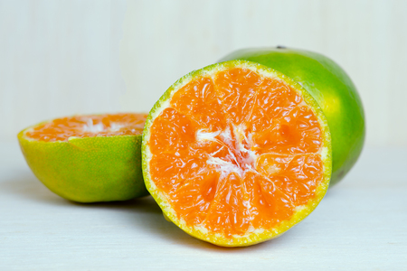 citrus     sinensis: Orange fruit (Other names are Les Oranger, sweet orange, citrus sinensis, Citrus aurantium, Citrus maxima, Citrus reticulate, mandarin orange) with half view isolated on wood background