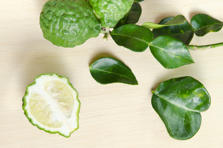 rutaceae: Bergamot (Also known as Kaffir lime, Citrus lime, Magnoliophyta Rutaceae) fruits and half cross section with leaf isolated on wood
