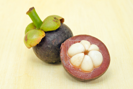 Mangosteen (Other names are garcinia, mangostana, clusiaceae, saptree, purple mangosteen, monkey fruit, Malpighiales) fruit with half cross section isolated on wooden board