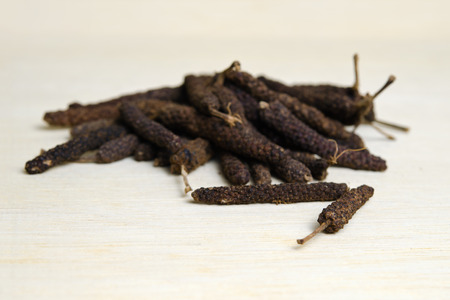 Long black pepper (Also called as Pipli in Indian, capsicum frutescens, Balinese pepper, Jaborandi pepper, Bengal pepper, Dipli in Thai, Piper longum) with mortar isolated on wood Stock Photo