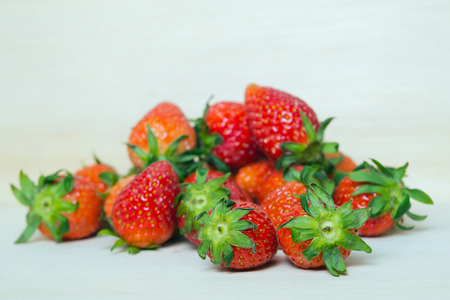 fragaria: Strawberry fruit with flash filled on wooden board (Other names are Fragaria strawberry, Fragaria ananassa)