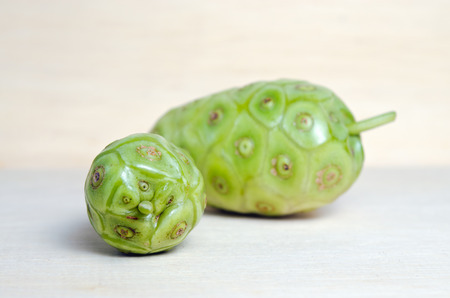 great morinda: Noni (Also named as Morinda Citrifolia, Rubiaceae Noni, great morinda, indian mulberry, beach mulberry, cheese fruit, Gentianales Noni) fruit with leaf isolated on wood background