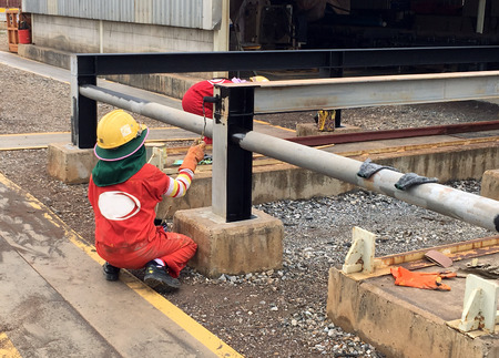offshore industry: Technician paints Pipe work structural steel in oil and gas offshore industry in a fabrication yard
