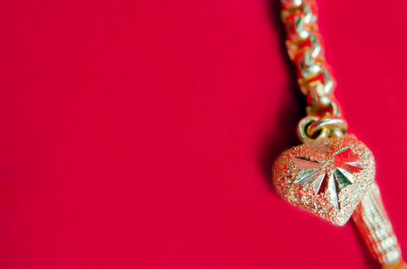 Gold necklace 96.5 precent Thai gold design with gold heart pendant isolated on red flannel cloth background with blank text copy space