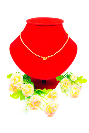 Gold necklace putting on red cloth with flowers isolated on white background