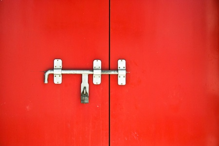old iron lock with bolt on the red door found in a temple in Thailand photo