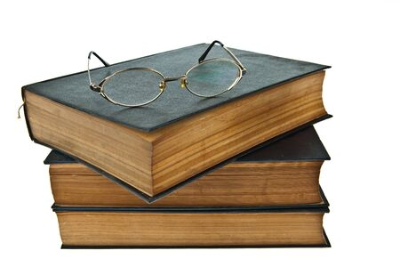 history books: Stack of old books with eye glasses isolated on white background Stock Photo