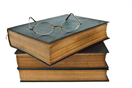 Stapel alter Bücher mit Brille isoliert auf weißem Hintergrund