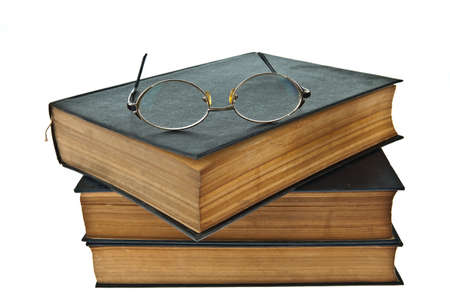 Stack of old books with eye glasses isolated on white background photo