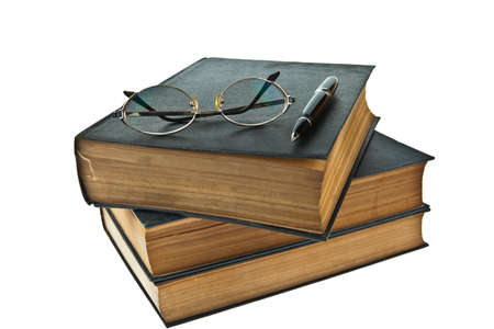 Stack of old books with eye glasses and pen isolated on white background photo