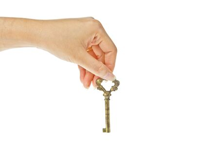Old golden key with hand isolated on white background photo