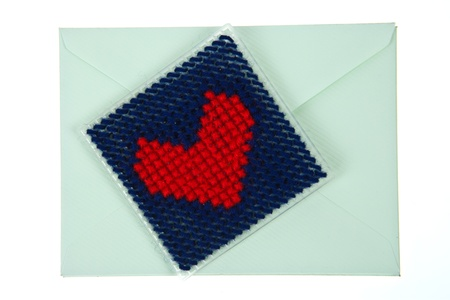 Green envelop with red knitted heart isolated on white background photo
