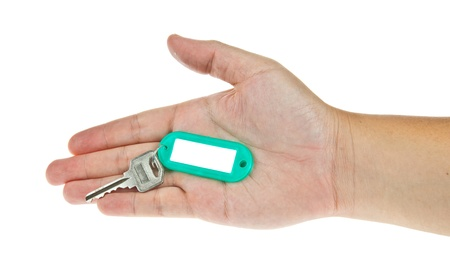 Key in hand with label isolated on white background photo
