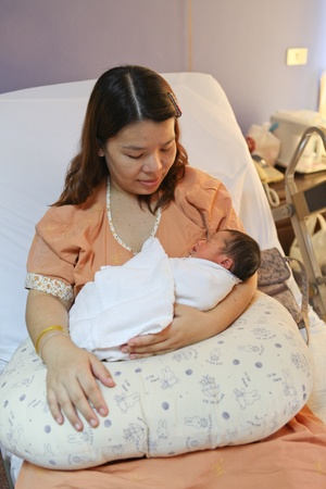 Sleeping baby with mother in a hospital photo