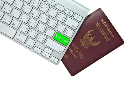 Green vacation button on computer keyboard with Thai passport isolated on white background photo