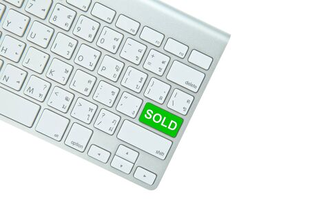 Green sold button on computer keyboard isolated on white background photo