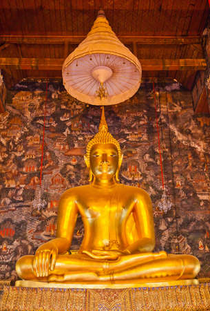 Golden Buddha statue in a temple in Thailand photo