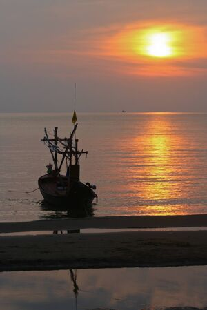 sillhouette: Sunset on the beach with boat