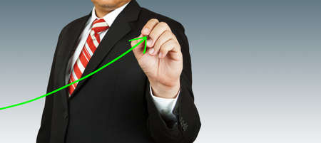 secure growth: businessman hand drawing chart green arrow