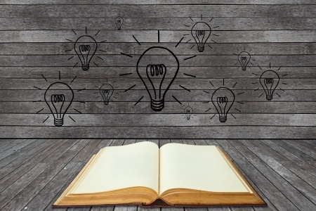 understand: Book and lightbulb in a wood room Stock Photo