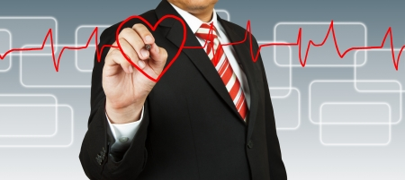 Businessman draw a pulse line with heart photo