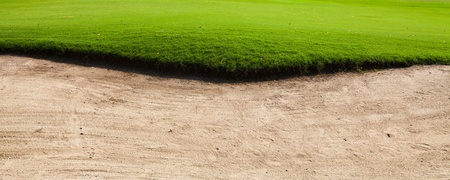 Sand bunker on the golf course with green grass photo