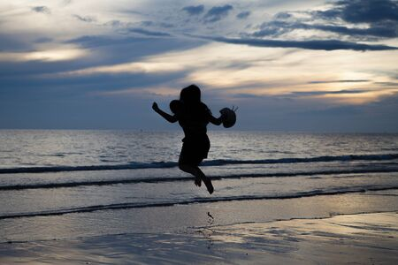 Silhouette Asian girl jump on beach photo