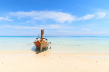 Boat on the beach with blue sky photo