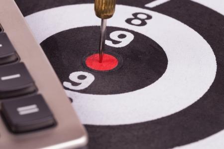 bulls eye target with dart and calculator photo