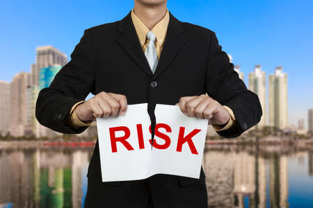 lost lake: Businessman tear paper with word Risk Stock Photo