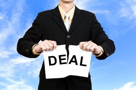 Businessman tear paper with word Deal on blue sky  Stock Photo