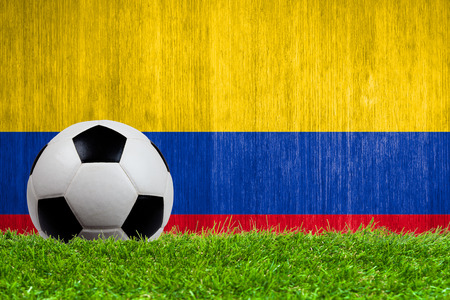 Soccer ball on grass with Colombia flag background close up